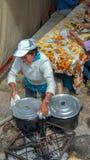 En kvinna som lagar mat på en träbrand arkivbild