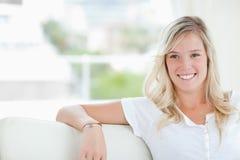 En kvinna som ler, som hon sitter på soffan arkivfoton