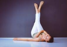 En kvinna som ligger på golvet med ben upp Arkivfoton