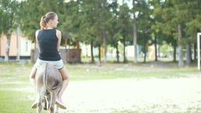 En kvinna som rider en åsna i stallen arkivfilmer