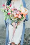En kvinna som rymmer en dekorativ bukett av blommor i hennes händer royaltyfri fotografi
