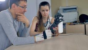 En kvinna som rymmer den bioniska armen som griper pappers- handdukar lager videofilmer