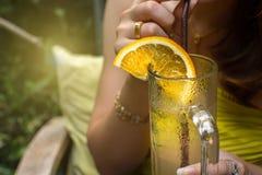En kvinna som rymmer ett exponeringsglas av lemonad f?r drink royaltyfri bild