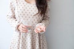 En kvinna som rymmer en medicin och ett exponeringsglas av vatten i hennes hand Medicinska och vård- begrepp royaltyfri fotografi