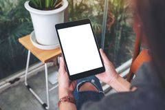 En kvinna som rymmer svart minnestavlaPC med den tomma vita sk?rmen, medan sitta i kaf? arkivfoton