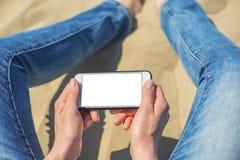 En kvinna som rymmer en vit mobiltelefon med en tom skärm royaltyfria foton