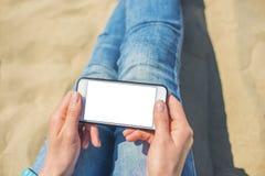 En kvinna som rymmer en vit mobiltelefon med en tom sk?rm royaltyfria foton