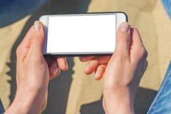 En kvinna som rymmer en vit mobiltelefon med en tom sk?rm arkivfoto