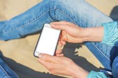En kvinna som rymmer en vit mobiltelefon med en tom sk?rm arkivfoton