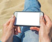 En kvinna som rymmer en vit mobiltelefon med en tom sk?rm royaltyfri bild