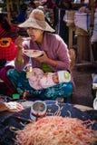 En kvinna som säljer frukter och grönsaker på en marknad Royaltyfri Fotografi