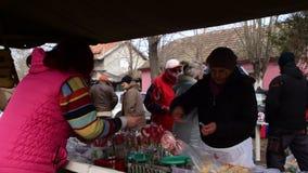 En kvinna som säljer sötsaker från en stall med färgrika godisar och klubbor på mässan lager videofilmer
