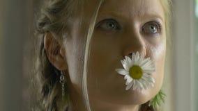 En kvinna som ser in i avståndet som rymmer en tusensköna i hennes mun lager videofilmer