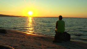 En kvinna som ser soluppgången över havet stock video