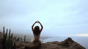 En kvinna som sitter av ett berg, mediterar och gör överst en gest med henne händer Maha Sakal Mot havet och arkivfilmer