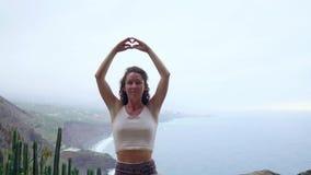 En kvinna som sitter av ett berg, mediterar och gör överst en gest med henne händer Maha Sakal Mot havet och stock video