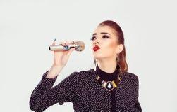 En kvinna som sjunger på mikrofonen arkivbilder