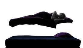 Kvinna som sovar i levitation på sängsilhouette Arkivbild