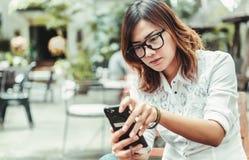 En kvinna som spelar mobiltelefonen Arkivfoto