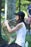 En kvinna som spelar en valthorn i Central Park Royaltyfri Bild