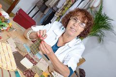 En kvinna som syr en patchwork Arkivfoto