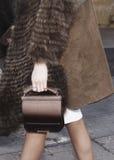 En kvinna som utomhus rymmer hennes kopplinghandväska Royaltyfri Foto