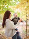En kvinna, ställningar i en höst parkerar bland träden och rymmer hennes lilla son som spelar med honom arkivbild