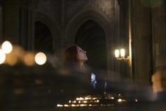 En kvinna står i en katolsk kyrka Närliggande bränner stearinljus Arkivbild
