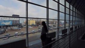 En kvinna står inre flygplatsbyggnad har glasväggar stock video