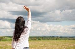 En kvinna står med hennes lyftta armar och ber till guden På ett grönt fält i sommar royaltyfri fotografi