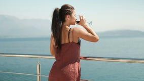 En kvinna står på balkongen med ett exponeringsglas och ser havet lager videofilmer