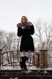 En kvinna står på farstubron mot en snöig skogvinter och den att snöa för ` s Royaltyfri Bild