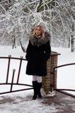 En kvinna står på farstubron mot en snöig skogvinter och den att snöa för ` s Arkivfoto