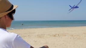En kvinna står på kusten på en varm solig dag och lanserar en ojämn nivå in i himlen En liten nivå flyger arkivfilmer