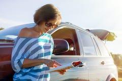 En kvinna står vid bilen på en landsväg Arkivfoto