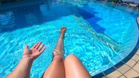 En kvinna svänger hennes ben, medan sitta bredvid simbassängen stock video