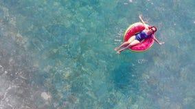 En kvinna svävar på en gummicirkel i havet h?rligt avslappnande kvinnabarn arkivfilmer