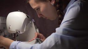 En kvinna syr kläder på en symaskin vid ljuset av en lampa Mode, skapelse och anpassa stock video