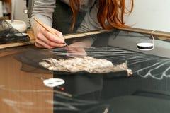 En kvinna syr pärlor på ett genomskinligt tyg Royaltyfri Fotografi