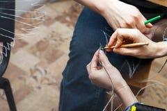 En kvinna syr pärlor på ett genomskinligt tyg Royaltyfria Bilder