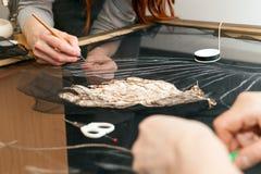 En kvinna syr pärlor på ett genomskinligt tyg Arkivfoto