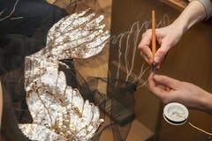 En kvinna syr pärlor på ett genomskinligt tyg Fotografering för Bildbyråer