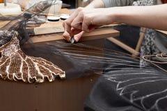En kvinna syr pärlor på ett genomskinligt tyg Arkivfoton