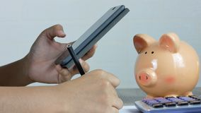 En kvinna tar anmärkningar och använder en smartphone med en droppe av pengar in i en spargris lager videofilmer