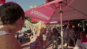 En kvinna tar av hennes hatt på en holifärgfestival stock video