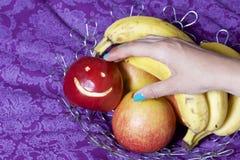 En kvinna tar ett rött äpple med en sniden emoticon från en maträtt Det finns en fruktkorg i bakgrunden Flera äpplen och banan royaltyfria bilder
