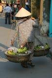 En kvinna transporterar bananer i korgar i en gata av Hoi An (Vietnam) Fotografering för Bildbyråer