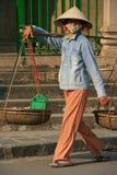 En kvinna transporterar gods i korgar i Hoi An (Vietnam) Arkivbild