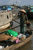 En kvinna transporterar gods på en roddbåt (Vietnam) Arkivfoton