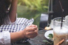 En kvinna tycker om att äta ostkaka och kaffe i kafé royaltyfria bilder
